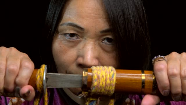 slow-motion-close-up-of-old-asian-woman-opening-sword