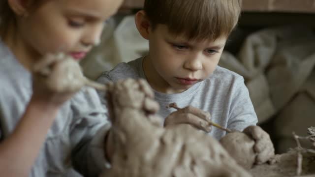 Chica-y-chico-esculpir-con-arcilla-cerámica