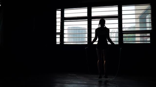 silueta-panorámica-joven-boxeadora-útil-en-manos-de-vendaje-envuelto-saltando-sobre-saltar-la-cuerda