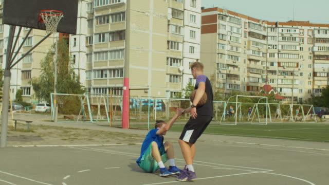 Jugadores-de-Streetball-ayudando-a-oponente-caído-a-levantarse