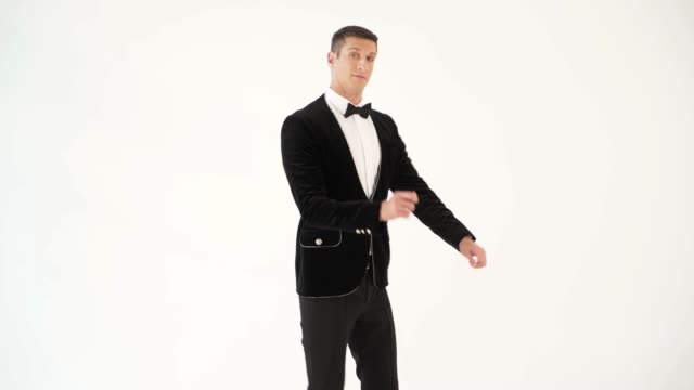 fun-man-in-a-black-suit-with-a-bow-tie-is-showing-dance-of-dancer-on-the-white-background