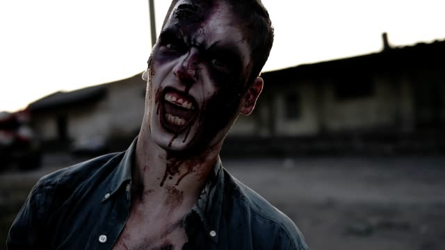 Portrait-of-a-male-zombie-with-bloody-teeth-and-wounded-face-screaming-and-shouting-Halloween-filming-staging-concept-Blurred-abandoned-town-on-the-background