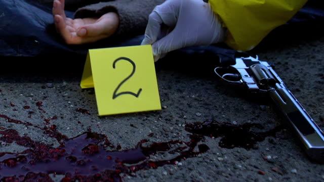 Médico-forense-señalando-evidencia-y-hacer-foto-de-la-víctima-accidente-de-tráfico