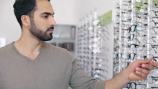 Tienda-de-gafas-Hombre-tratando-de-gafas-en-la-tienda-de-óptica