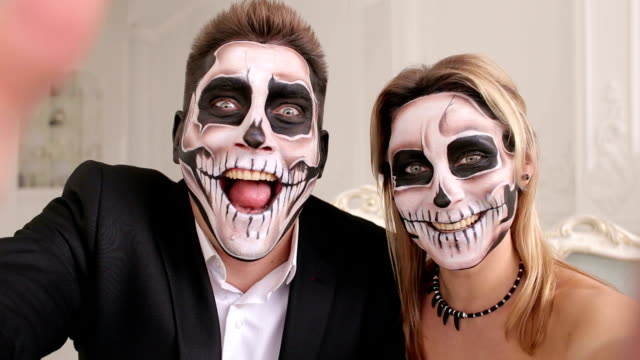 Creepy-couple-with-scary-Halloween-makeup-make-selfies-in-a-studio-