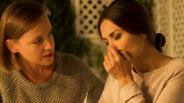 Two-sisters-supporting-each-other-in-grief-dealing-with-family-loss-closeup
