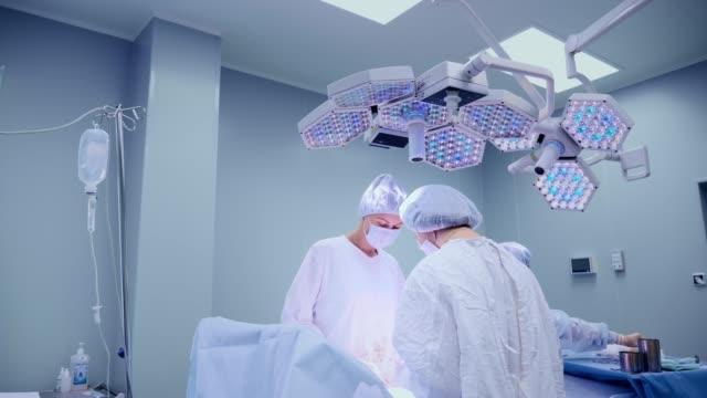 Ärzteteam-chirurgische-Tätigkeit-in-hellen-modernen-OP-Saal-