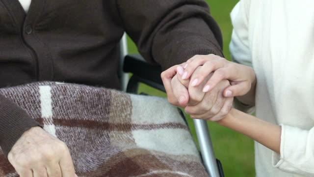 Mujer-de-la-mano-del-paciente-en-silla-de-ruedas-programa-de-voluntariado-concepto-de-la-caridad