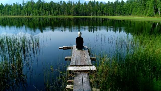 Una-chica-sentada-en-el-borde-de-un-muelle-de-madera-cerca-de-las-aguas-tranquilas-de-un-lago-del-bosque