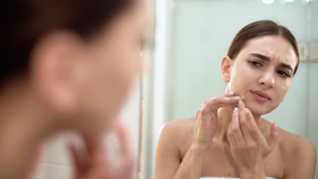 Problema-de-la-piel-Mujer-de-mancha-en-la-cara-y-mirarse-en-espejo-de-trituración