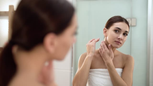 Skin-Care-Woman-Touching-Face-And-Looking-At-Mirror-At-Bathroom