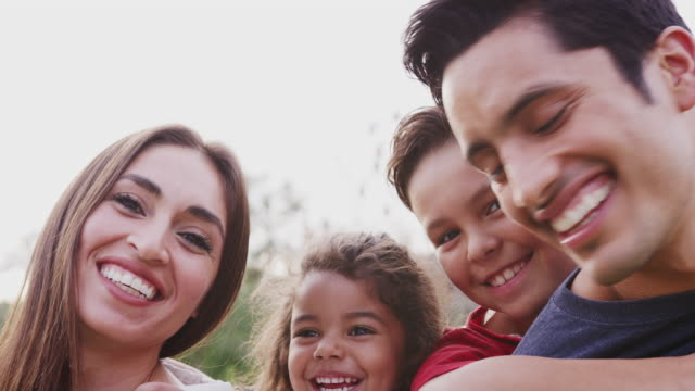 Head-and-shoulders-close-up-of-smiling-young-Hispanic-parents-piggybacking-their-children-in-park