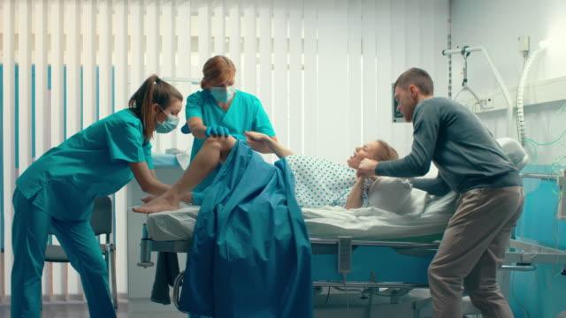 In-der-Krankenhaus-Frau-Geburt-hält-Mann-ihre-Hand-in-der-Unterstützung-Geburtshelfer-unterstützen-Moderne-Lieferung-Ward-mit-professionellen-Hebammen-