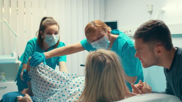 En-el-Hospital-la-mujer-dando-a-luz-marido-tiene-su-mano-en-apoyo-obstetras-ayudando-Entrega-moderna-sala-con-parteras-profesionales-