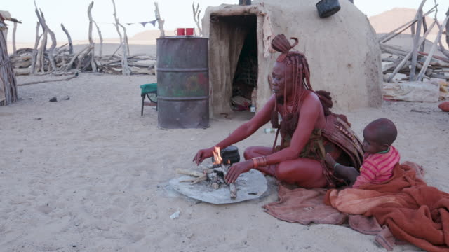 4K-view-of-Himba-woman-in-traditional-dress-with-young-child-putting-a-small-pot-on-a-fire-outside-their-hut-within-their-small-compound-Namibia