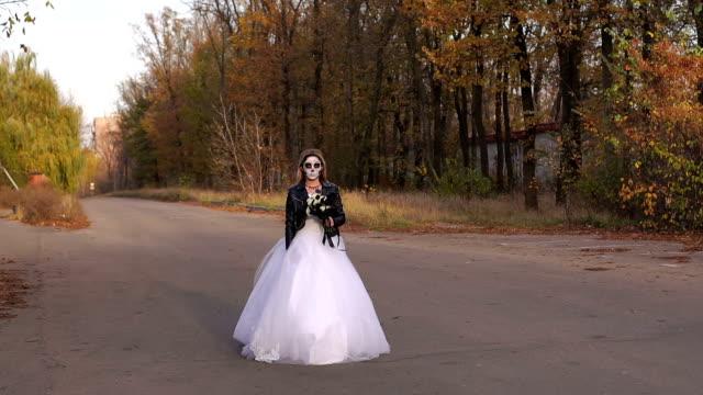 Una-chica-joven-con-un-maquillaje-espeluznante-en-forma-de-un-cráneo-que-va-en-un-camino-vacío