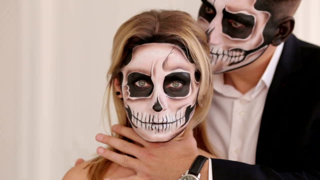 A-man-with-Halloween-makeup-is-holding-his-girlfriend-by-the-neck-