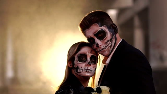 Couple-with-dark-skull-makeup-on-the-background-of-burning-fire-and-smoke-