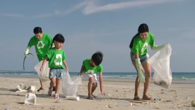 Gruppe-von-Freiwilligen-in-grünen-T-Shirts-putzen-den-Strand-mit-Plastiktüten-voller-Müll-die-Zeitlupe-Sichere-Ökologie-Konzept-4k-Auflösung-