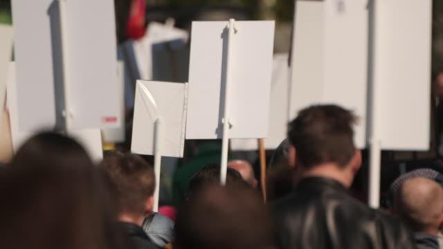 Activistas-multitudinarios-en-un-mitin-con-carteles-están-en-la-carretera-caminando-por-Estados-Unidos-