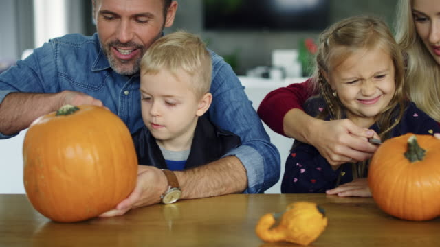Eltern-helfen-Kindern-beim-Kürbisschnitzen