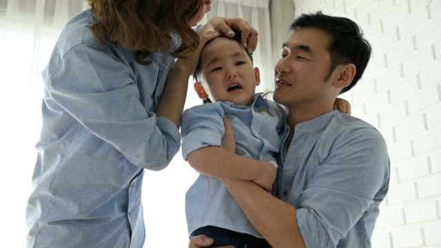 Parents-came-to-comfort-half-Japanese-boy-after-slipped-and-his-head-hit-by-floor-until-he-cried-Happy-family-and-baby-of-Multi-ethnics-mixed-race-people-concept-Appreciate-parenthood-and-child
