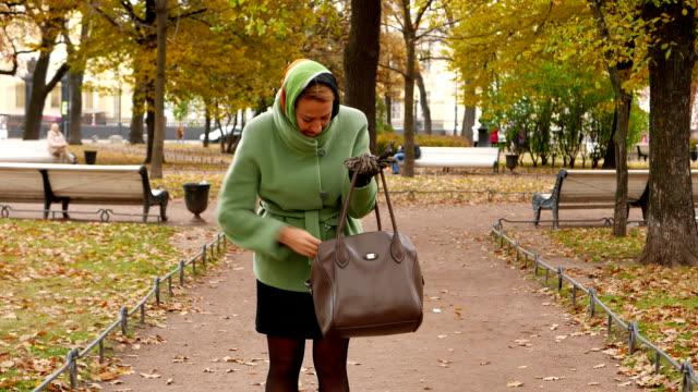 Mujer-intenta-encontrar-en-el-bolso-buscar-llamada-de-teléfono-recoger-y-responder-a