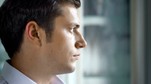 Sad-disappointed-man-looking-out-of-the-window