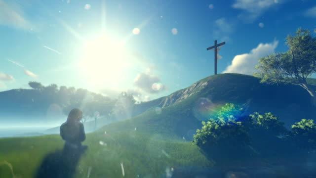 Woman-praying-at-Jesus-cross-against-beautiful-morning-sun-panning