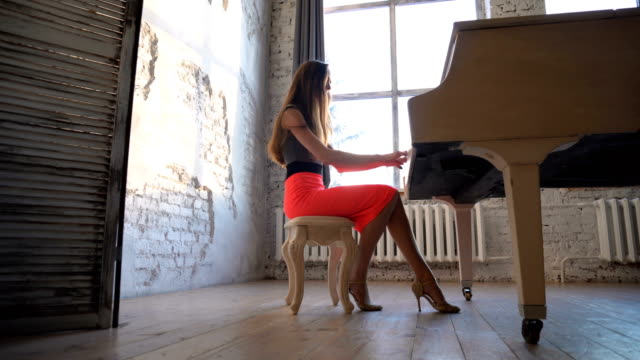 Young-woman-comes-and-sits-down-at-the-piano-to-play-it-