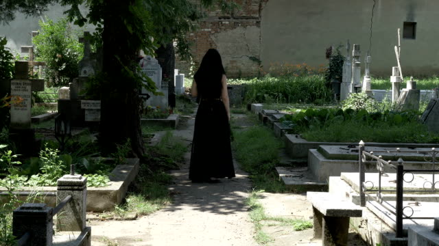 Creepy-woman-walking-in-cemetery-alley-to-beloved-grave-and-placing-a-crown-on-grave