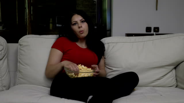 Bored-young-woman-sitting-on-the-couch-and-eating-popcorn-while-watching-TV-in-the-evening