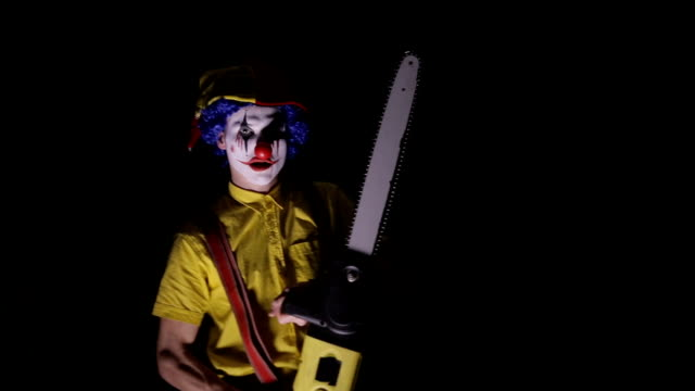 A-clown-comes-out-of-the-dark-with-a-chainsaw-