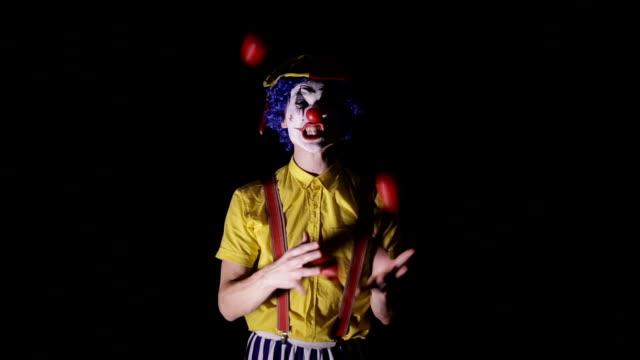 A-clown-juggles-red-apples-and-shows-his-teeth-