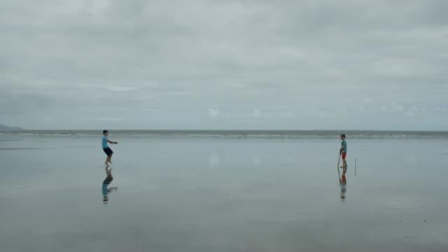 -Fuera-Dos-niños-pequeños-jugando-cricket-de-playa-el-jugador-de-bolos-golpea-el-wicket-