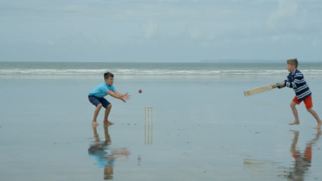 Two-young-boys-playing-beach-cricket-one-trying-to-get-in-and-the-other-hits-the-stumps-