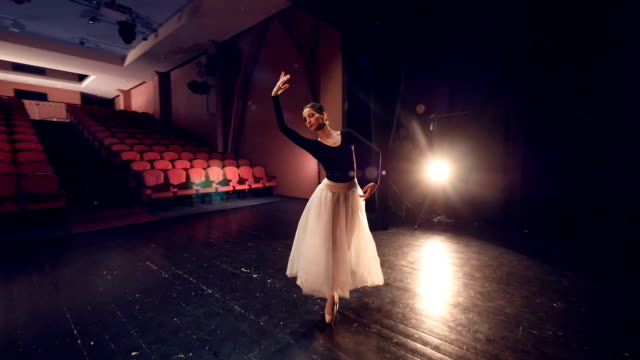 Una-bailarina-que-da-vuelta-alrededor-en-el-centro-de-un-escenario-vacío-