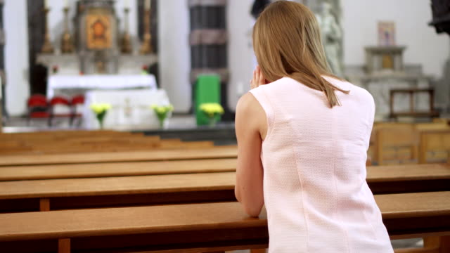 Young-devoted-religious-woman-praying-in-catholic-church-Faithful-catholic-at-european-cathedral