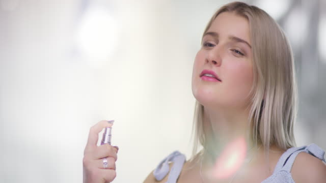Close-Portrait-of-beautiful-young-Woman-spraying-on-Perfume-on-neck