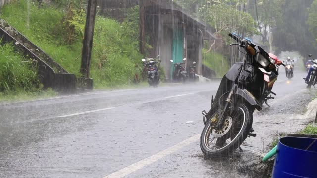 Traffic-along-a-typical-street-on-the-road-during-the-rain-in-Ubud-island-Bali-Indonesia