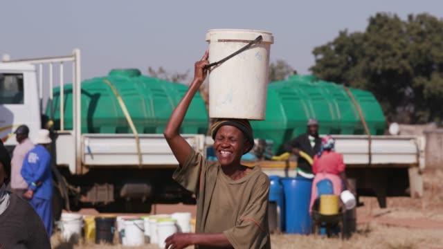Dos-mujer-africana-recogiendo-agua-de-una-cisterna-en-baldes-plásticos-y-caminando-hacia-sus-casas