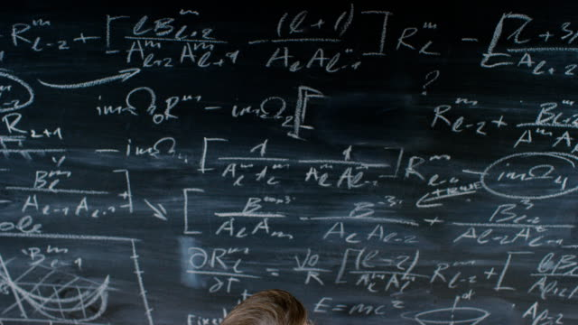High-Angle-Shot-of-a-Brilliant-Young-Student-Writing-Big-Sophisticated-Mathematical-Formula/-Equation-on-the-Blackboard-