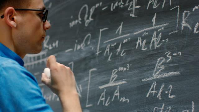Brillante-matemático-joven-escribe-complejas-matemáticas-ecuación-/-fórmula-en-la-pizarra-