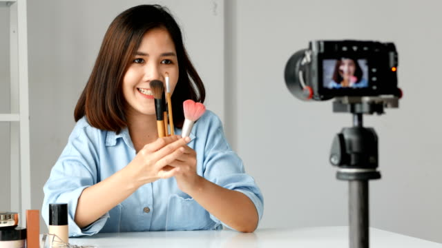 Young-asian-woman-influencer-beauty-fashion-blogger-recording-video-Presen-her-product-shooting-on-camera-