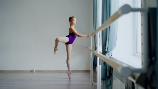 Cámara-lenta-de-poco-bailarín-de-ballet-clásico-de-puntillas-de-pie-y-levantando-la-pierna-hacia-atrás-practicando-solo-en-ballet-barre-en-luz-salón-de-baile-en-estudio-de-arte-