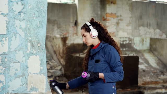 Kreative-junge-Frau-Graffiti-Maler-nutzt-Paint-Spray-um-zerstörten-Pfeiler-in-alten-leeren-Lagerhalle-zu-schmücken-Mädchen-hört-Musik-über-Kopfhörer-