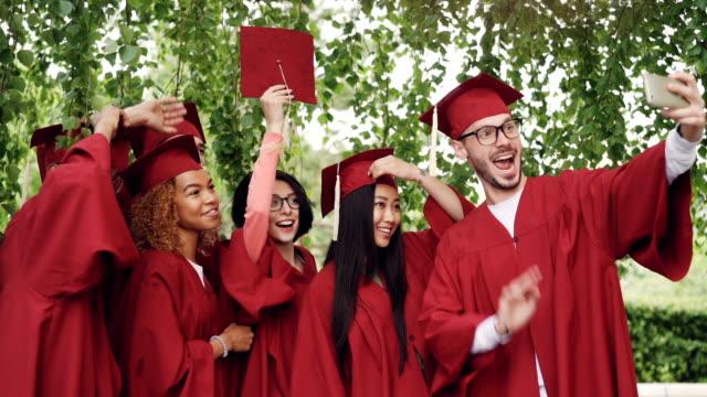 Graduierenden-Studenten-Mädchen-und-Jungs-sind-Einnahme-Selfie-am-Abschlusstag-Mortarboards-und-Kleider-tragen-junger-Mann-hält-Smartphone-andere-stellen-