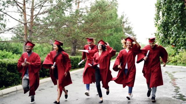 Slow-Motion-der-emotionalen-Absolventen-glückliche-Mädchen-und-Jungs-mit-Diplomen-und-lachen-hübsches-Mädchen-ist-Doktorhut-ausziehen-und-schwenken-Kleinen-Regen-ist-sichtbar
