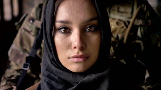 Retrato-cerca-de-mujer-musulmana-hijab-mirando-a-cámara-soldado-armado-con-la-situación-del-arma-detrás-de-mujer-concepto-militar