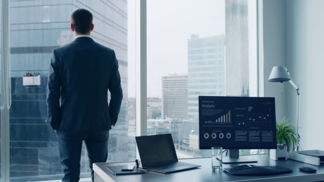 Thoughtful-Businessman-in-a-Suit-Standing-in-His-Office-Looking-out-of-the-Window-and-Contemplating-Next-Big-Business-Contract-Major-City-Business-District-with-Panoramic-Window-View-